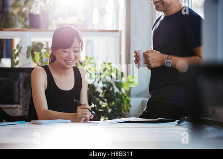 Shot of smiling young woman sitting at her desk working with male colleague standing by. Business people at work - Stock Photo