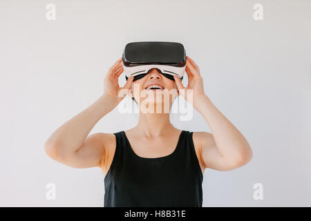 Shot of young woman using the virtual reality headset and smiling against grey background. Happy female model wearing - Stock Photo