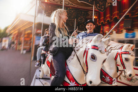 Smiling man and woman on amusement park carousel. Young couple on horse carousel ride at fairground. - Stock Photo