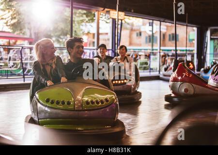 Young people driving bumper car at fairground. Young friends having fun riding bumper car at amusement park. - Stock Photo