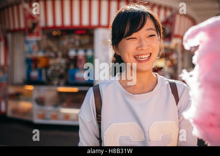 Shot of young asian woman at amusement park with cotton candy floss. Smiling female with candyfloss at fairground. - Stock Photo