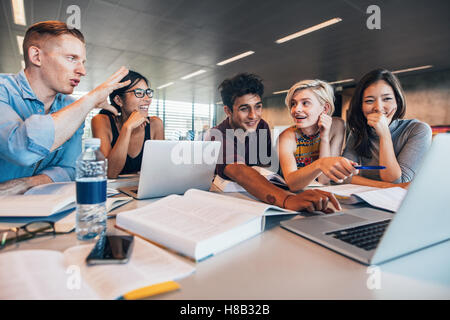 University students using laptop in a library. Students working together on academic project finding information - Stock Photo