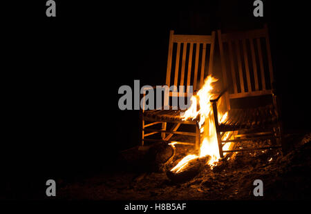 Fire that is burning on a pair of old rocking chairs - Stock Photo
