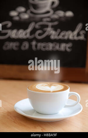 Good cup of coffee and good quote behind - Stock Photo