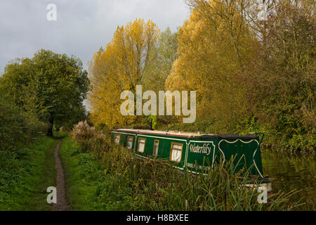A narrow boat moored by the towpath of the Kennet & Avon Canal on Hungerford Common in autumn, October - Stock Photo