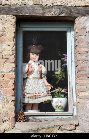 Old porcelain doll at the window at the rural village of Carona on Switzerland - Stock Photo