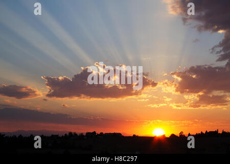 Setting sun with rays created by the shadows of the clouds. - Stock Photo