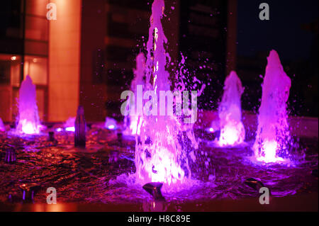 Illuminated colored night fountain in the city - Stock Photo