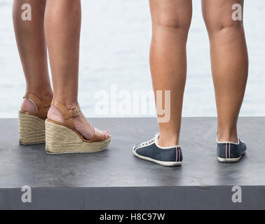 Low angle view of two woman wearing different kinds of footwear: heels and flat. - Stock Photo
