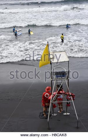 Lifeguard post tower on Playa la Cicer beach and surfers in Las Palmas Gran Canaria Canary Islands Spain - Stock Photo