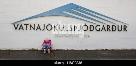 A young girl sits outside the visitor centre at Skaftafell National Park in sourtheastern Iceland - Stock Photo