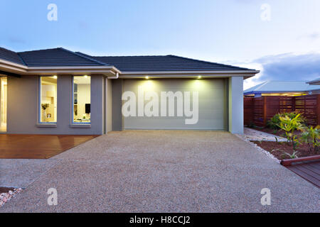 Part of this luxury house includes a garage with a white door and illuminated by two small lights under the ceiling. - Stock Photo