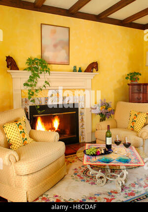 Yellow sitting room with fireplace, wine on glass table and armchairs in Provence Style, LÕAuberge Provencale Inn, - Stock Photo
