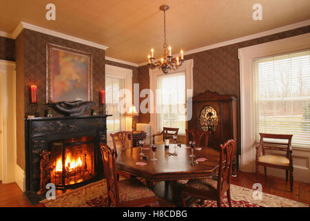 Wooden Table And Chairs In Front Of Fireplace Lit Fire