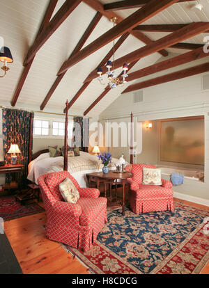 Pair of red upholstered armchairs at foot of four poster bed in a barn-themed bedroom. - Stock Photo