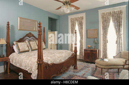 Wooden four poster double bed in blue bedroom. - Stock Photo