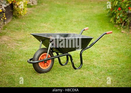 gardeners wheelbarrow standing on a lawn - Stock Photo