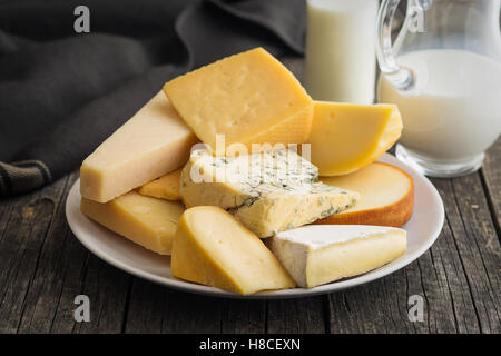 Different kinds of cheeses on old wooden table. - Stock Photo