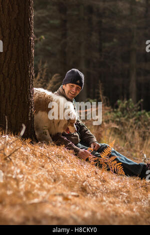 Man and dog enjoying the outdoors together hiking looking happy having fun in the woods amongst nature in autumn - Stock Photo