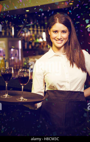 Composite image of portrait of pretty waitress serving red wine - Stock Photo