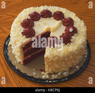 Red velvet cake with a piece missing on the table - Stock Photo