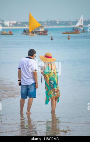 PORTO GALINHAS, BRAZIL, JANUARY - 2016 - Young adult couple at shore of beach in Porto Galinhas, Pernambuco, Brazil - Stock Photo