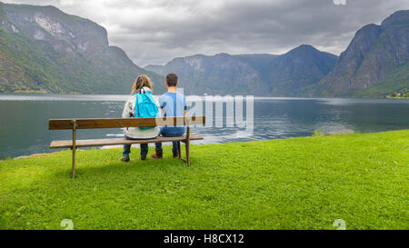 Mother and son sitting on a bench  looking at the fjord in Ulvik,  Norway - Stock Photo