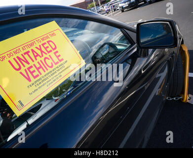 DVLA wheelclamp and serve a notice on an untaxed car left in the car park of the Metro Centre shopping mall, Newcastle, - Stock Photo