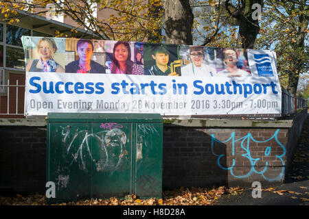 'Success starts in Southport' college enrollment sign above graffiti covered wall, Southport, Merseyside, UK. - Stock Photo