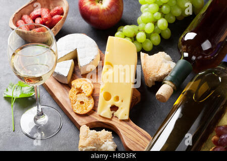 White wine, grape, bread and cheese on stone table. Focus on wine glass - Stock Photo