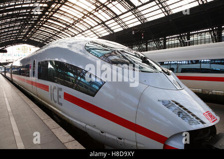 An Intercity Express train of Deutsche Bahn stays in the Cologne train Station in Germany - Stock Photo