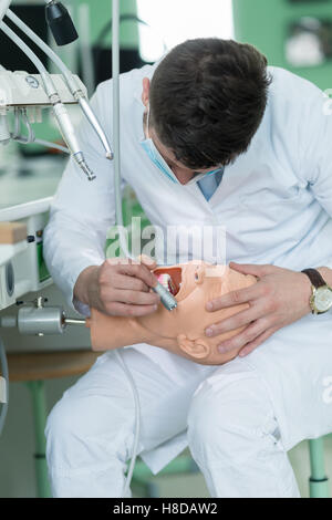 Male dental student practicing on doll. - Stock Photo