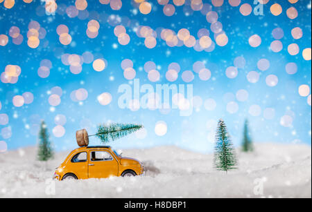 Miniature car carrying a Christmas tree in snow. Concept of Christmas - Stock Photo