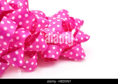 closeup of some gift puff bows made with pink ribbon patterned with white dots, on a white background - Stock Photo