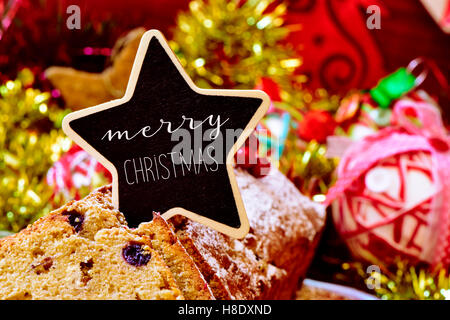 closeup of a fruitcake topped with a star-shaped signboard with the text merry christmas, on a table full of christmas - Stock Photo