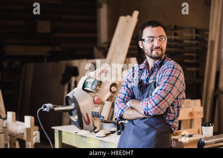Happy young handyman carpenter in workshop, smiling - Stock Photo