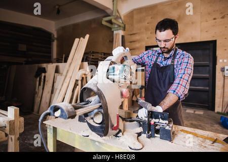 Carpenter Using Circular Saw for wood at his workshop - Stock Photo