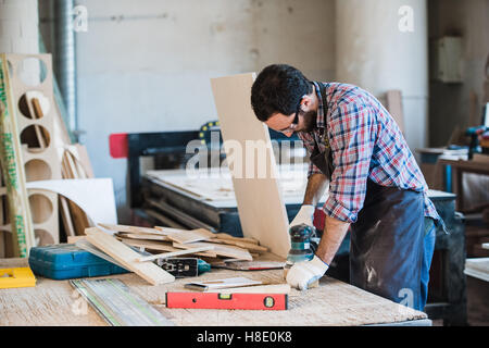 Carpenter with power grinder at his workshop - Stock Photo
