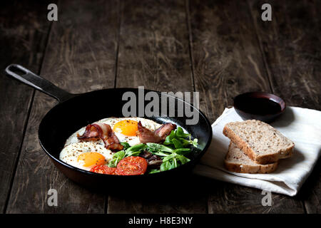 Breakfast set. Pan of fried eggs with bacon, fresh tomato, sage and bread on dark serving board over black wooden - Stock Photo