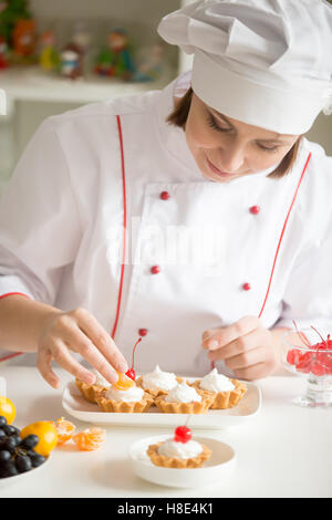 Professional female confectioner decorating mini fruit tarts - Stock Photo