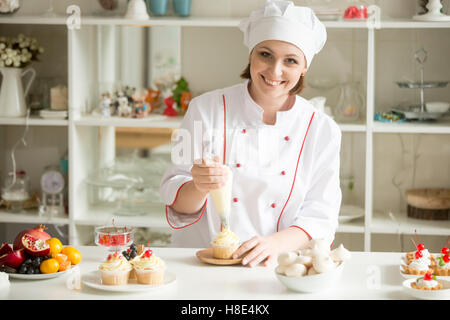 Portrait of female confectioner topping a cupcake with cream - Stock Photo