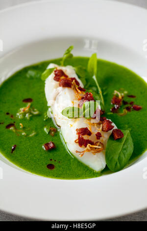 Butter poached cod with green peas, spinach and basil veloute, crispy chorizo and shallots - Stock Photo