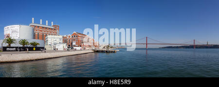 Lisbon, Portugal. Central Tejo, historical power plant and Electricity Museum with the 25 de Abril bridge  over - Stock Photo