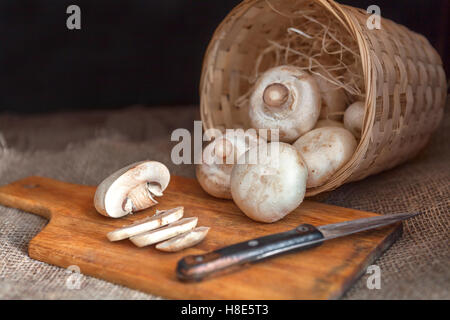 White mushrooms closeup sliced, lying on a cutting wooden board with a knife. Wicker basket full of champignon - Stock Photo