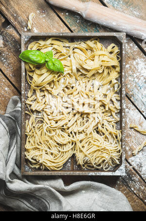 Various homemade fresh uncooked Italian pasta with flour and green basil leaves in wooden tray over shabby background, - Stock Photo