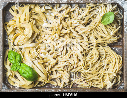Various homemade fresh uncooked Italian pasta with flour and green basil leaves in wooden tray, top view, horizontal - Stock Photo