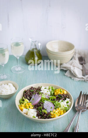 Roasted Poblano Quinoa Salad served with queso fresco, cilantro dressing. Photographed on a light blue/green background - Stock Photo