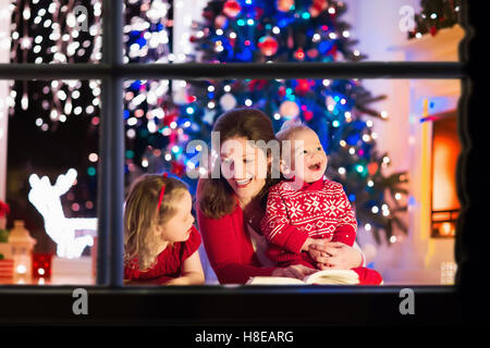 Family on Christmas eve at fireplace. Mother and little kids opening Xmas presents. Children with gift boxes. - Stock Photo