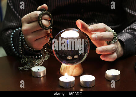 sorcerer hands over a transparent crystal ball fortune-telling for future - Stock Photo