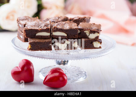 Valentines day cheesecake brownies on cake stand on pink roses background - Stock Photo